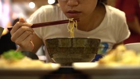 4K ασιατική γυναίκα που χρησιμοποιεί τα ραβδιά για την κατανάλωση του νουντλς βόειου κρέατος, κινεζικά τρόφιμα εστιατορίων απόθεμα βίντεο