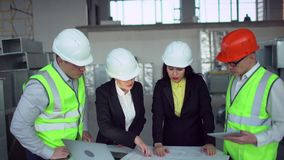 4k βέβαιος θηλυκός μηχανικός ή αρχιτέκτονας που συζητά τα ζητήματα κατασκευής με τους άνδρες συνάδελφοι πράσινες φανέλλες απόθεμα βίντεο