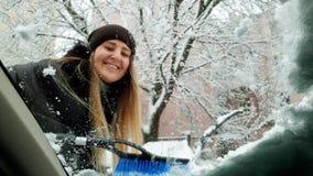 4k βίντεο άποψης του όμορφου χαμόγελου νέου αλεξήνεμου αυτοκινήτων γυναικών καθαρίζοντας από το χιόνι με τη βούρτσα φιλμ μικρού μήκους