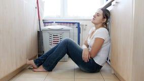 4k βίντεο βράσης της εξαντλημένης νέας συνεδρίασης γυναικών στο πάτωμα μετά από να πλύνει τα ενδύματα και να κάνει τα οικιακά απόθεμα βίντεο