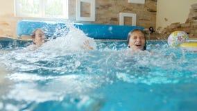 4k βίντεο δύο εύθυμων αδελφών που παίζουν στην πισίνα και το καταβρέχοντας νερό απόθεμα βίντεο
