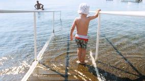 4k βίντεο λίγου αγοριού toddelr που περπατά στη θάλασσα στην ξύλινη κεκλιμένη ράμπα με τα κιγκλιδώματα απόθεμα βίντεο