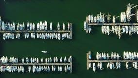 4K βίντεο σύνταξης Πτήση πέρα από τη μαρίνα με τα δεμένους γιοτ, τα σκάφη και το φάρο, εναέρια άποψη ματιών πουλιών ` s στο ηλιοβ απόθεμα βίντεο