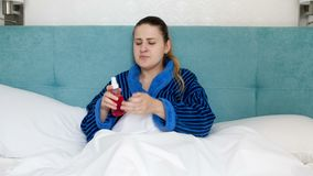 4k βίντεο της άρρωστης γυναίκας στο μπουρνούζι που βρίσκεται στο κρεβάτι και την ψεκάζοντας ιατρική στο λαιμό απόθεμα βίντεο