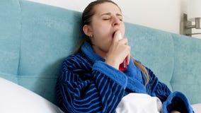 4k βίντεο της άρρωστης γυναίκας στο μπουρνούζι που βρίσκεται στο κρεβάτι και που παίρνει τον ψεκασμό λαιμού απόθεμα βίντεο