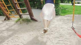 4K βίντεο της ευτυχούς χαμογελώντας γυναίκας στη φούστα που έχει τη διασκέδαση στην ταλάντευση στο πάρκο απόθεμα βίντεο
