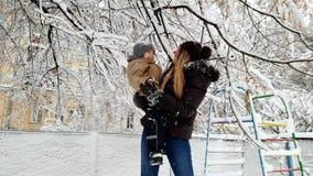 4k βίντεο της ευτυχούς χαμογελώντας νέας γυναίκας που κρατά το αγόρι μικρών παιδιών της και που παίζει με το χιόνι στο χειμερινό  απόθεμα βίντεο