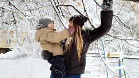 4k βίντεο της νέας μητέρας που κρατά το γιο μικρών παιδιών της και που τινάζει τους κλάδους δέντρων που καλύπτονται με το χιόνι Ο απόθεμα βίντεο
