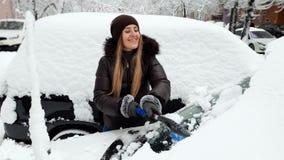 4k βίντεο της όμορφης χαμογελώντας νέας γυναίκας που αφαιρεί το χιόνι από το αυτοκίνητό της με το brish στο χώρο στάθμευσης φιλμ μικρού μήκους