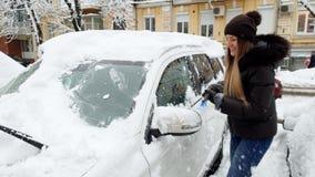 4k βίντεο της όμορφης χαμογελώντας νέας γυναίκας που αφαιρεί το χιόνι από το αυτοκίνητό της με το brish στο χώρο στάθμευσης απόθεμα βίντεο