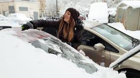 4k βίντεο της όμορφης χαμογελώντας νέας γυναίκας που καθαρίζει το αυτοκίνητό της από το χιόνι με την τηλεσκοπική βούρτσα απόθεμα βίντεο