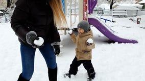 4k βίντεο του παιχνιδιού αγοριών μικρών παιδιών γέλιου με τη νέα μητέρα στο playgrund που καλύπτεται με το χιόνι Οικογένεια που ρ απόθεμα βίντεο