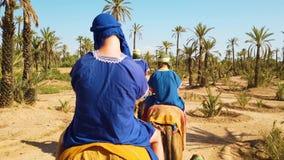 4K βίντεο του τροχόσπιτου καμηλών στην έρημο Σαχάρας, Μαρόκο Άνθρωποι στο μπλε που ντύνουν τις βεδουίνες καμήλες γύρου στους αμμό απόθεμα βίντεο