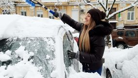 4k βίντεο του χαμογελώντας θηλυκού οδηγού που αφαιρεί το χιόνι από το αυτοκίνητό της στο πρωί μετά από τη χιονοθύελλα απόθεμα βίντεο