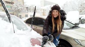 4k βίντεο του χαμογελώντας θηλυκού οδηγού που αφαιρεί το χιόνι από το αυτοκίνητό της στο πρωί μετά από τη χιονοθύελλα φιλμ μικρού μήκους