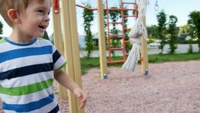 4k βίντεο του χαριτωμένου μικρού παιδιού που ρίχνει και που προσπαθεί να πιάσει το μεγάλο σχοινί για την αναρρίχηση στην παιδική  απόθεμα βίντεο