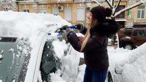 4k βίντεο του όμορφου θηλυκού οδηγού που καθαρίζει το αυτοκίνητό της από το χιόνι μετά από τη χιονοθύελλα στο πρωί απόθεμα βίντεο
