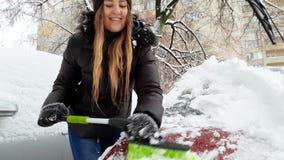 4k βίντεο του όμορφου χαμόγελου νέου ανεμοφράκτη αυτοκινήτων γυναικών καθαρίζοντας από το χιόνι με τη βούρτσα απόθεμα βίντεο
