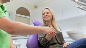 4k βίντεο των ευτυχών χεριών τινάγματος γυναικών χαμόγελου με τον οδοντίατρο μετά από την επεξεργασία δοντιών απόθεμα βίντεο