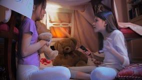 4k βίντεο δύο κοριτσιών που λένε τις τρομακτικές ιστορίες με το φακό στο μόνος-γίνοντα σπίτι στην κρεβατοκάμαρα απόθεμα βίντεο