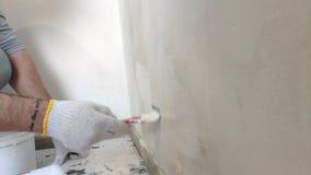 4K γενειοφόρο άτομο που χρωματίζει τους εσωτερικούς τοίχους στο επίπεδο που χρησιμοποιεί τη βούρτσα χρωμάτων Όμορφος νεαρός άνδρα
