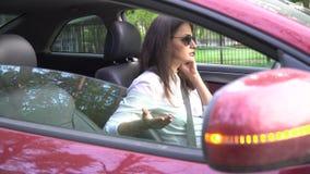 4K γυναίκα που μιλά στο τηλέφωνο κυττάρων στο αναλύω αυτοκίνητο απόθεμα βίντεο