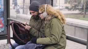 4K ελκυστικοί νεαρός άνδρας και γυναίκα που εξετάζουν το κινητό τηλέφωνο περιμένοντας σε μια στάση λεωφορείου φιλμ μικρού μήκους