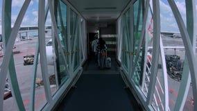 4k επιβάτες που επιβιβάζονται μέσω του jetway και εισγμένος αεροπλάνου για να τραπεί σε φυγή απόθεμα βίντεο
