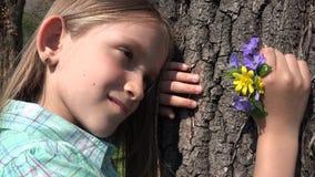 4K ευτυχές παιχνίδι πορτρέτου παιδιών στο πάρκο, πρόσωπο κοριτσιών με τα λουλούδια άνοιξη στη φύση φιλμ μικρού μήκους