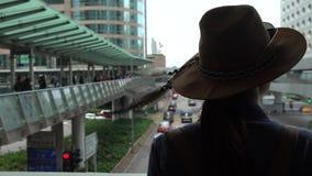 4K η ασιατική γυναίκα τουριστών φορά ένα καπέλο στη για τους πεζούς γέφυρα του Χονγκ Κονγκ κεντρική απόθεμα βίντεο