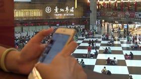 4K η ασιατική γυναίκα cheack το τηλέφωνο, πλήθος των ταξιδιωτών ανθρώπων αγοράζει το εισιτήριο τραίνων απόθεμα βίντεο
