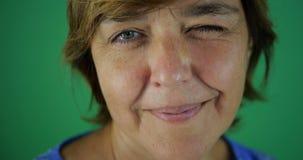 4k - Η μέσης ηλικίας γυναίκα με ένα σύντομο κούρεμα κλείνει το μάτι και χαμογελά στο πράσινο στοκ εικόνα
