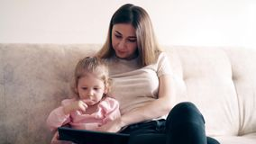 4k: Η νέα χαριτωμένα μητέρα και το μικρό κορίτσι κάθονται στον καναπέ και διδάσκουν χρησιμοποιώντας έναν υπολογιστή ταμπλετών φιλμ μικρού μήκους