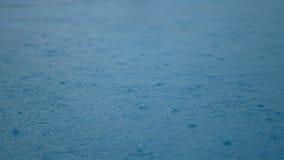 4K η πτώση βροχής μήκους σε πόδηα κινηματογραφήσεων σε πρώτο πλάνο στη σαφή μπλε επιφάνεια νερού με τον ουρανό και τα σύννεφα απε απόθεμα βίντεο