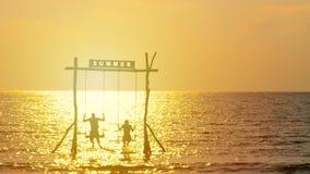 4K η σκιαγραφία του ευτυχούς ζεύγους απολαμβάνει με την ταλάντευση πέρα από τη θάλασσα κατά τη διάρκεια του χρόνου ηλιοβασιλέματο φιλμ μικρού μήκους