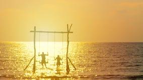 4K η σκιαγραφία του ευτυχούς ζεύγους απολαμβάνει με την ταλάντευση πέρα από τη θάλασσα κατά τη διάρκεια του χρόνου ηλιοβασιλέματο απόθεμα βίντεο