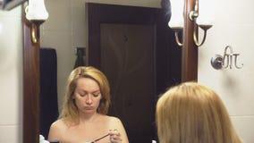 4K κίνηση αργή Μια γυναίκα χρωματίζει τα eyelashes της μπροστά από έναν καθρέφτη στο λουτρό φιλμ μικρού μήκους