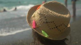 4k, κινηματογράφηση σε πρώτο πλάνο το κορίτσι σε ένα καπέλο αχύρου εξετάζει τα κύματα της θάλασσας E o απόθεμα βίντεο