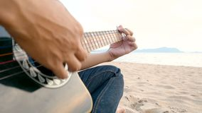4K κλείστε επάνω ενός ατόμου που παίζει την ακουστική κιθάρα στην παραλία κατά τη διάρκεια του χρόνου ηλιοβασιλέματος, το αίσθημα φιλμ μικρού μήκους