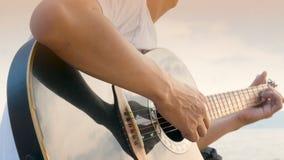4K κλείστε επάνω ενός ατόμου που παίζει την ακουστική κιθάρα στην παραλία κατά τη διάρκεια του χρόνου ηλιοβασιλέματος, το αίσθημα απόθεμα βίντεο