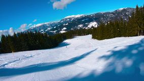 4K μήκος σε πόδηα ενώ ο σκιέρ πηγαίνει κάτω στη βουνοπλαγιά απόθεμα βίντεο