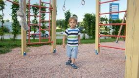 4k μήκος σε πόδηα λίγου αγοριού μικρών παιδιών που παίζει στην παιδική χαρά με το μεγάλο σχοινί για την αναρρίχηση απόθεμα βίντεο