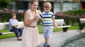 4k μήκος σε πόδηα λίγου αγοριού todler που κρατά τη μητέρα του με το χέρι περπατώντας στο υψηλό στηθαίο στο πάρκο φιλμ μικρού μήκους