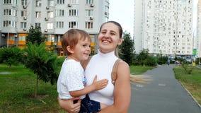 4k μήκος σε πόδηα της ευτυχούς χαμογελώντας νέας μητέρας που κρατά το γιο μικρών παιδιών της και που τρέχει στην οδό φιλμ μικρού μήκους