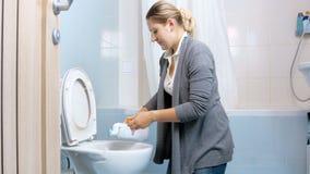 4k μήκος σε πόδηα της νέας γυναίκας που χύνει το αντιβακτηριακό απορρυπαντικό στην τουαλέτα κάνοντας τα οικιακά απόθεμα βίντεο
