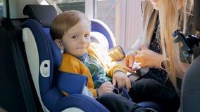4k μήκος σε πόδηα της νέας μητέρας που ξεσφίγγει τις ζώνες και που παίρνει το γιο μωρών της από το κάθισμα αυτοκινήτων ασφάλειας  απόθεμα βίντεο