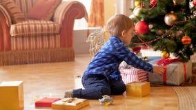 4k μήκος σε πόδηα της συνεδρίασης μικρών παιδιών κάτω από το χριστουγεννιάτικο δέντρο και να φωνάξει λόγω του ανεπιθύμητου παρόντ φιλμ μικρού μήκους