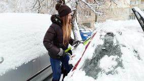 4k μήκος σε πόδηα της χαμογελώντας νέας γυναίκας που καθαρίζει το αυτοκίνητό της από το χιόνι πρίν οδηγά στην εργασία απόθεμα βίντεο