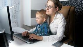 4k μήκος σε πόδηα της όμορφης κομψής επιχειρηματία που εργάζεται στον υπολογιστή με το λατρευτό γιο μικρών παιδιών της στο γραφεί φιλμ μικρού μήκους