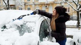 4k μήκος σε πόδηα της όμορφης χαμογελώντας νέας γυναίκας που αφαιρεί το χιόνι από το αυτοκίνητό της με τη βούρτσα Καθαρίζοντας αυ απόθεμα βίντεο